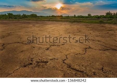 sunset above cracked soil - stock photo