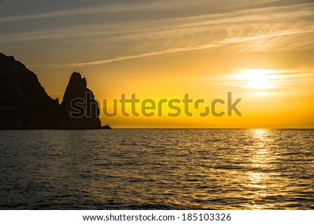 Sunset above the sea with rocks and orange sky - stock photo