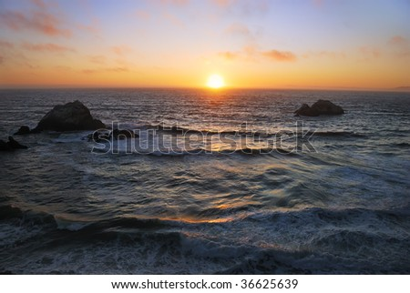 Sunset above the wavy Pacific as seen from the Ocean Beach in San Francisco, California. - stock photo