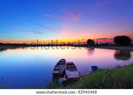 Sunset along the pond with two boats under magical sky in Hong Kong - stock photo