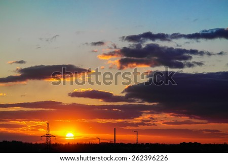 sunset among the clouds in the blue sky above the city - stock photo