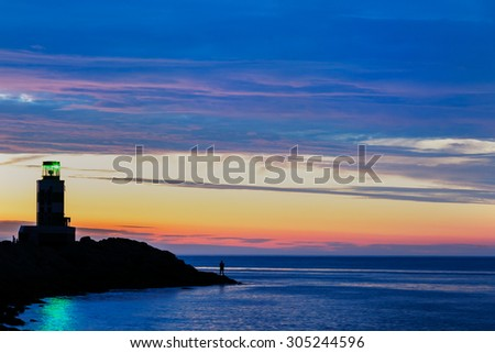 Sunset and a lonely fisherman and lighthouse - stock photo