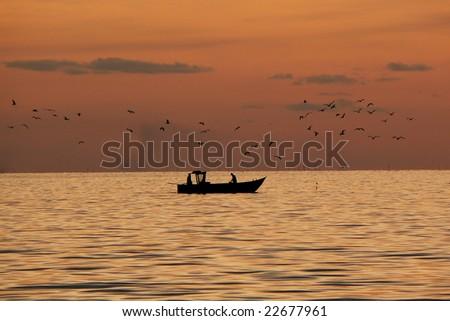Sunset and fishing boat in Umag-Croatia - stock photo
