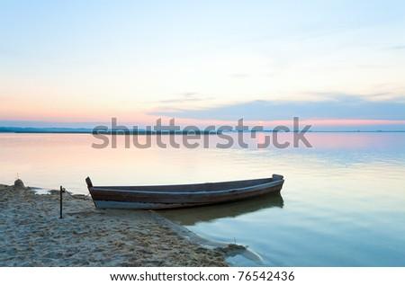 Sunset and old wooden fishing boat near the summer lake shore (Svityaz, Ukraine) - stock photo