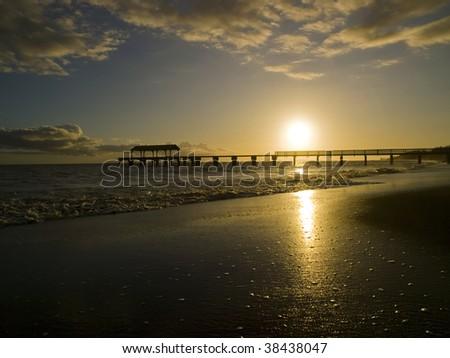 Sunset and pier on the beach at the Kauai, Hawaii - stock photo