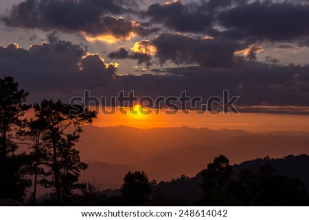 Sunset and saturation color sky.Tree,cloud and mountain in shadow.Foreground are silhouette.