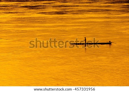 Sunset and silhouette of a fisherman in a boat. - stock photo