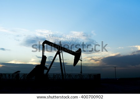 Sunset and silhouette of crude oil pump in oilfield - Bahrain  - stock photo
