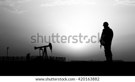 Sunset and silhouette of oilfield worker with crude oil pump background in oilfield - black and white - stock photo
