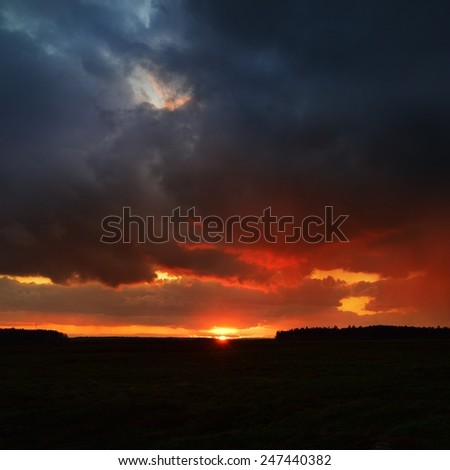 Sunset and the dramatic rain clouds over countryside landscape. Autumn in Latvia. - stock photo