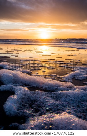 sunset and water reflection on beach - stock photo