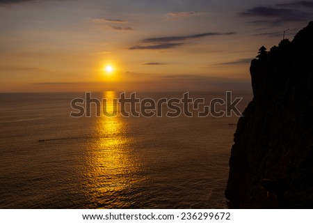 Sunset at a cliff in Bali Indonesia. - stock photo