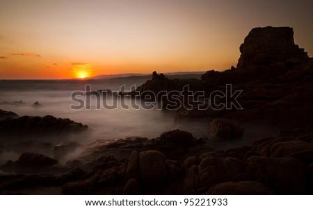 Sunset at a rock beach in Tonnara, Corsica - stock photo