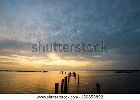 sunset at a weathered pier at port charlotte harbor, near punta gorda,  southwest florida - stock photo