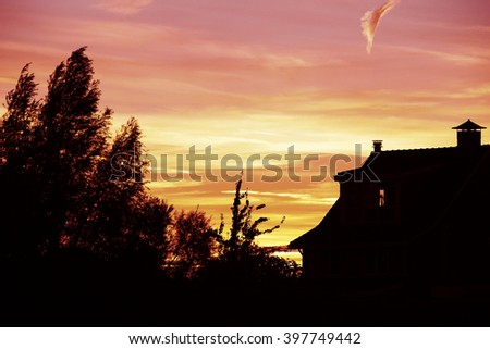 Sunset at Dutch house with trees - stock photo
