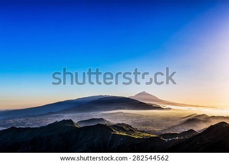Sunset at evening in mountains and blue sky with haze and Teide volcano on background in Tenerife Canary island, Spain