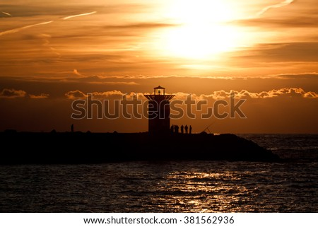 Sunset at lighthouse. Nice bright sunset sky and a pier with people on it.