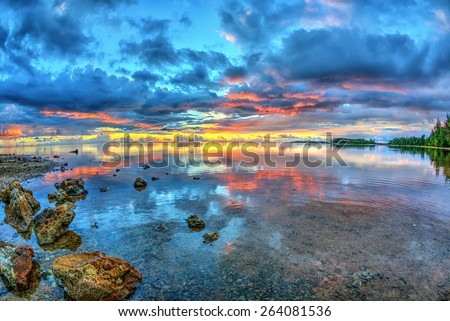 Sunset at low tide with still waters and the rocky coastline of Guam - stock photo