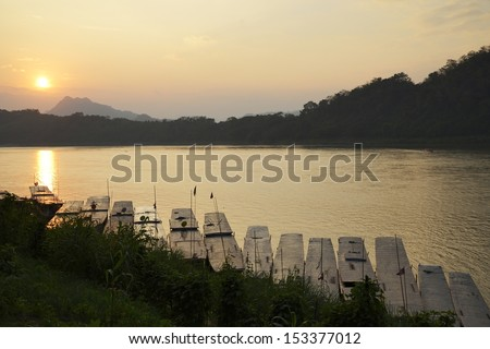 sunset at Mekong River - sunset on Mekong River is shown in circa Jan. 2013 in Luang Prabang, Laos, which is a famous river in southeast Asia - stock photo