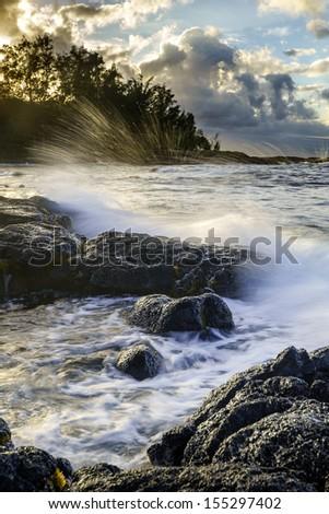 Sunset at ocean coast in Hilo, Hawaii, Big Island. - stock photo