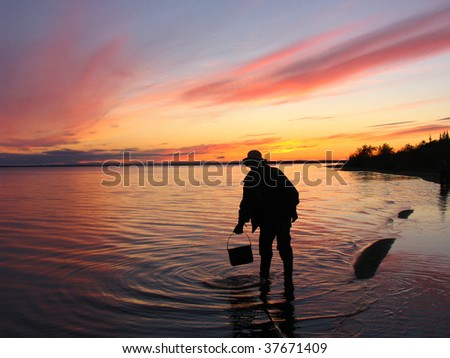 Sunset at river Ob at Polar circle with silhouette of a fisherman - stock photo