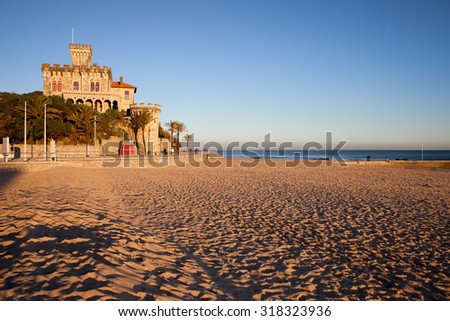 Sunset at sandy Tamariz beach by the Atlantic Ocean in resort town of Estoril, municipality of Cascais, Portugal.