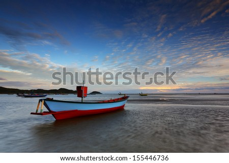 Sunset at seen the fishing boat - stock photo