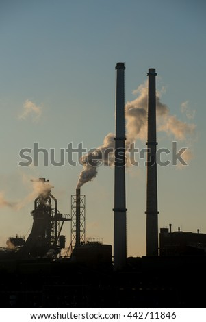 Sunset at steel factory showing several smoke chimneys