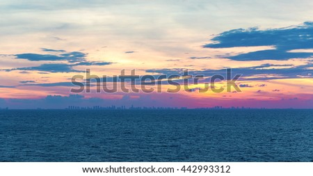 Sunset at the caribbean sea and a panoramic view of Miami beach skyline silhouette. - stock photo