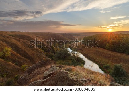 Sunset at the hills by the river in autumn. Ukraine
