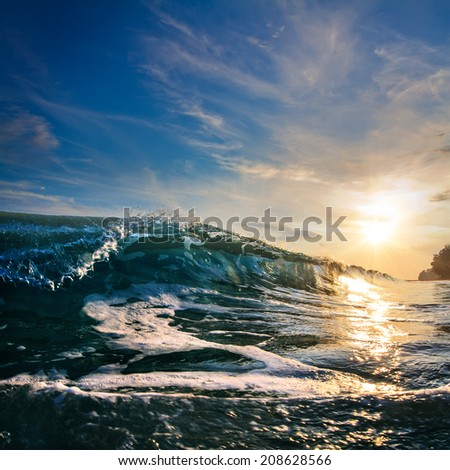 Sunset at the sea with beautiful green wave