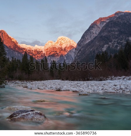 Sunset at the Soca river with snowy mountains in the background