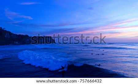 Sunset at Uluwatu, a famous surf spot in the south of Bali, Indonesia with beautiful blue sky background