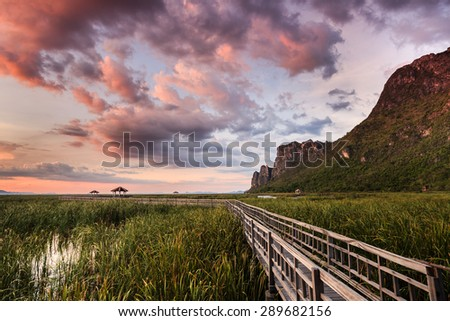 Sunset at Wooden path with pavilion on the marshes near the rock mountain.
