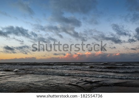 Sunset Baltic sea shore with a dramatic mood - stock photo