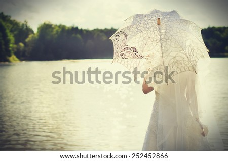 Sunset, beautiful bride with an umbrella on a background of water - stock photo