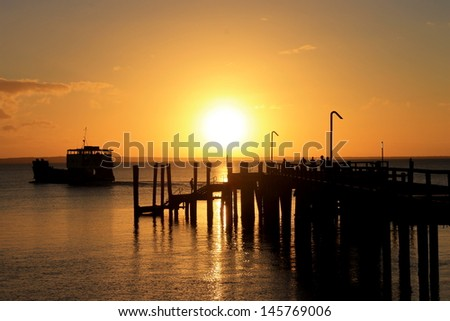 Sunset behind jetty and ferry on Fraser Island, Queensland, Australia. - stock photo