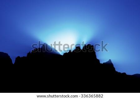 sunset behind mountain blue background - stock photo