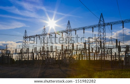 Sunset behind substation towers. - stock photo