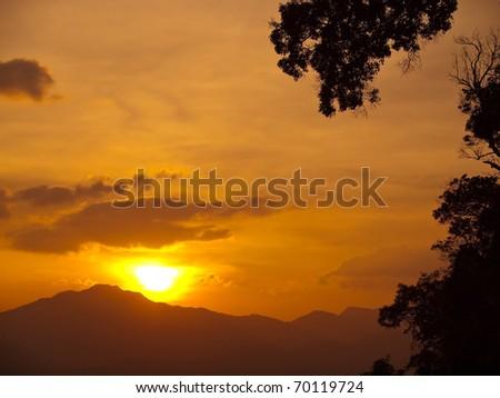 sunset behind the mountains range with orange sky - stock photo