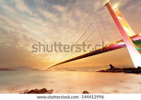Sunset cityscape with famous Tsing Ma bridge over water in Hong Kong, Asia. - stock photo