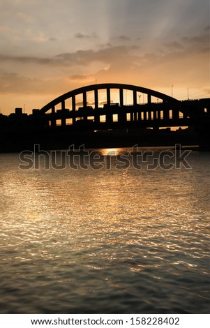 Sunset cityscape with silhouette of bridge under golden dramatic sky in Taipei, Taiwan, Asia.