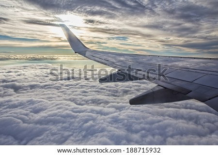 Sunset, cloudy sky and airplane wing as seen through window of an aircraft.