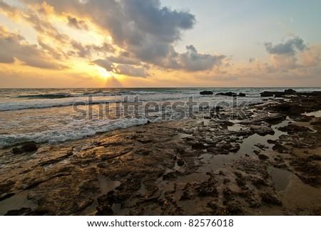sunset from  rocky beach - stock photo