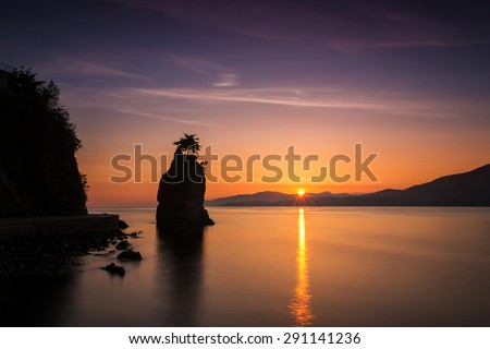 sunset from stanley park, vancouver, bc, with a silhouette of siwash rock - stock photo