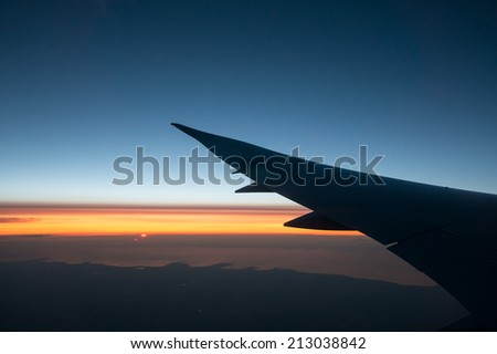 Sunset from the plane window with the left wing on the foreground