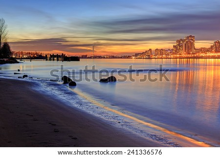 Sunset glow and city lights reflecting over river water and beach