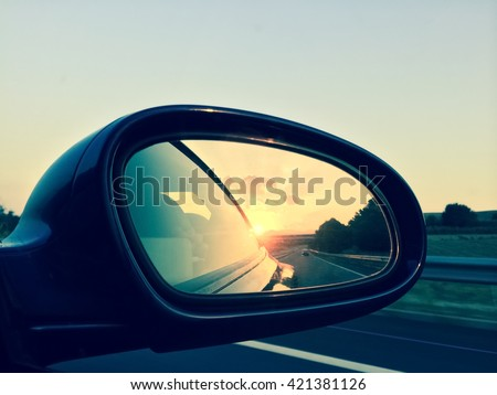 Sunset in a rear view mirror. Modern car on a highway. - stock photo