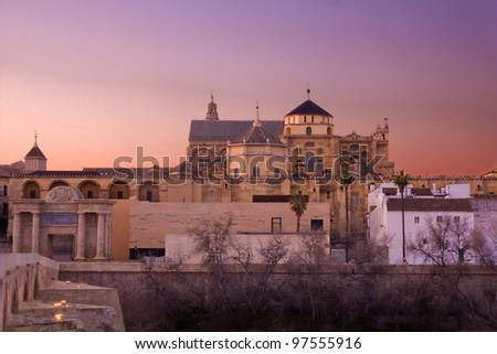 Sunset in Cordoba, Andalusia, Spain. The cathedral and the mosque in the main focus. On the left, the triunphal arch and the Roman bridge. - stock photo