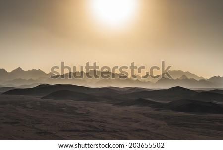 Sunset in desert mountains - stock photo